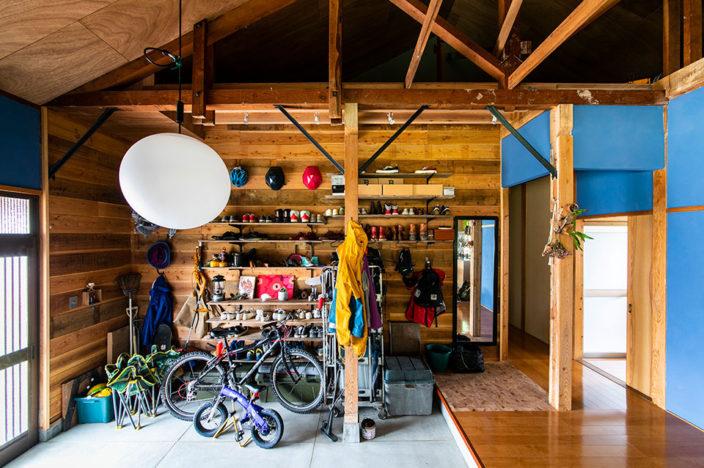 子供の玩具、恒平さんの工具、アウトドアグッズ、自転車などがシューズとともに置かれた玄関スペース