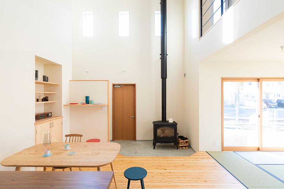 玄関の一角には東島夫妻の念願だった薪ストーブが堂々と鎮座する。東島邸 里山建築