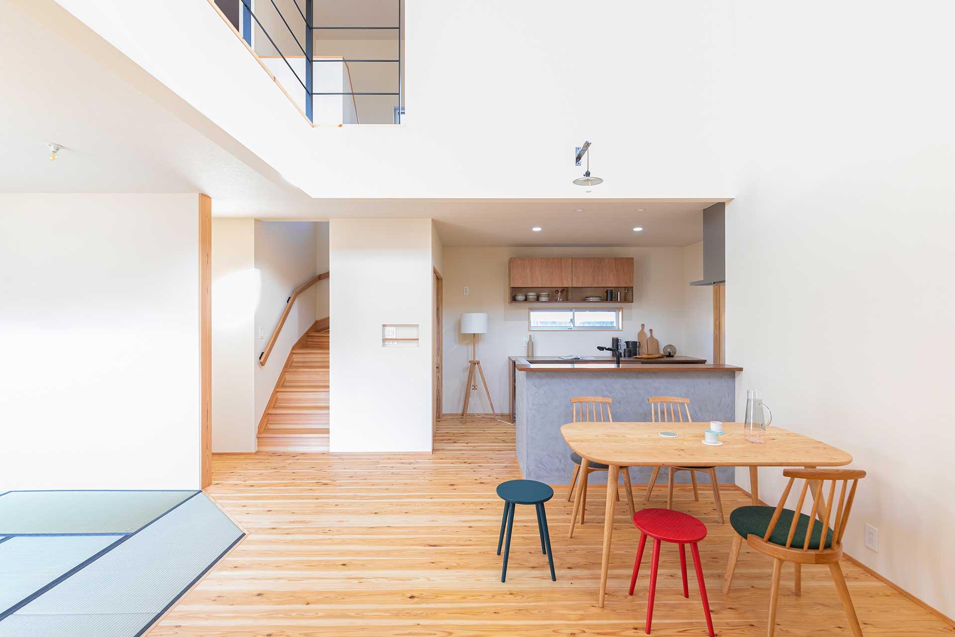 リビングを見渡せるキッチンは作業スペースを挟んでその対面にある作業台を兼ねた収納棚との間隔がゆったりと設ける。東島邸 里山建築