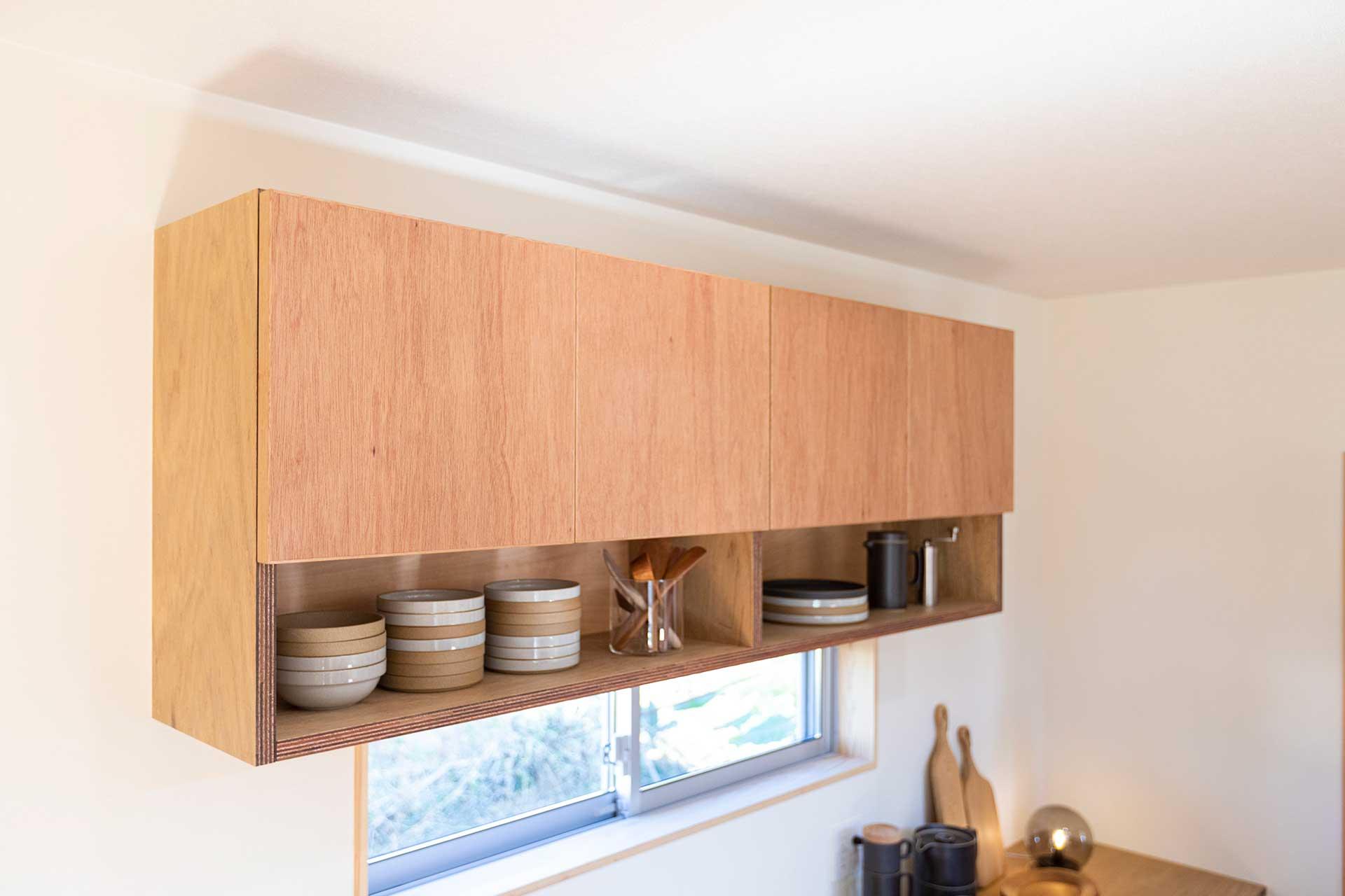 キッチンの収納棚にはラワン材の合板を取り入れ、あえて塗装せず、木目をそのまま見せる方法を採用した。東島邸 里山建築