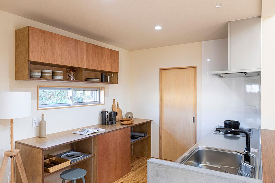 そのキッチンと店舗との境界に設けた勝手口の戸を開くと、そこには土間仕様のパントリー。東島邸 里山建築